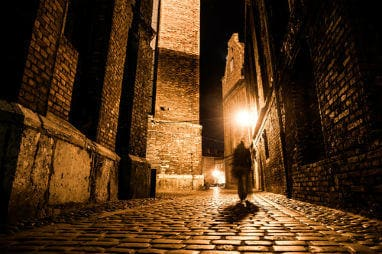 _european_halloween_destinations_-dark_blurred_silhouette_of_person_evokes_jack_the_ripper_in_illuminated_cobbled_street_in_old_historical_city_by_night_resized