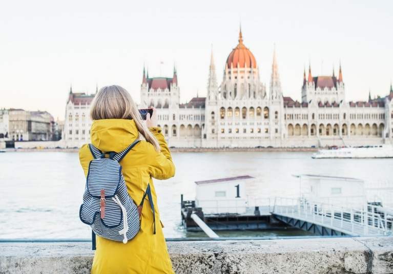 Blonde girl with a yellow coat and stripey backpack is taking a photo of the Budapest Parliament building across the river Danube