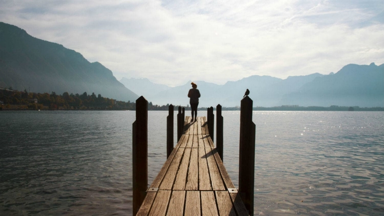 example_interrail_trip_-_girl_standing_on_a_wooden_platform_at_the_lake_geneva_switzerland_5