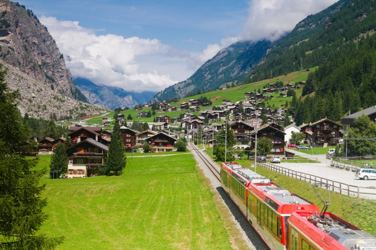 The red Glacier Express train cuts through traditional timbered buildings in a deep valley