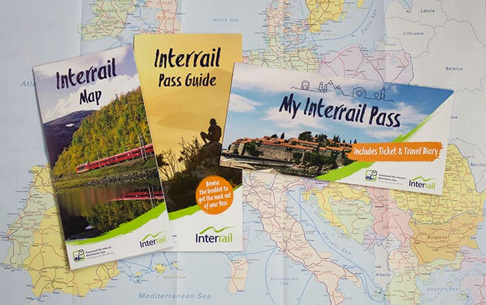 Image of the Interrail Travel Pack including an Interrail Pass Guide, Pass Cover, and Map laid on a map of Europe.