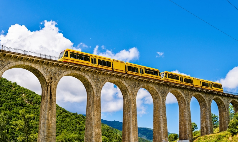 View of a yellow train crossing a viaduct in a green valley with a blue sky