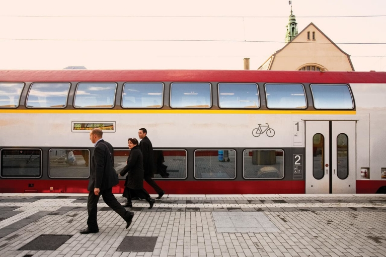 Image of 3 people walking along a train plaform in Luxembourg next to a stationary double decker train