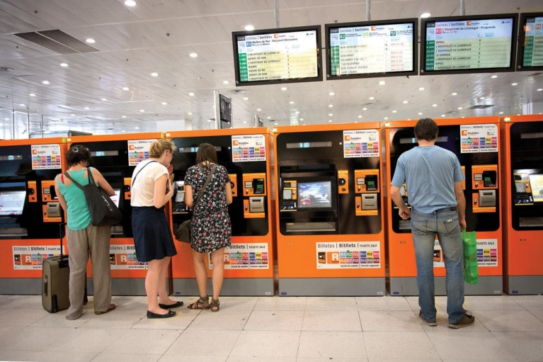 Image of people using ticket machines and a departure board in Barcelona station