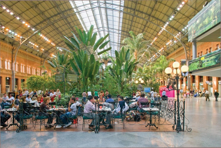 People sitting on a terrace at Atocha Railway Station in Madrid, Spain.