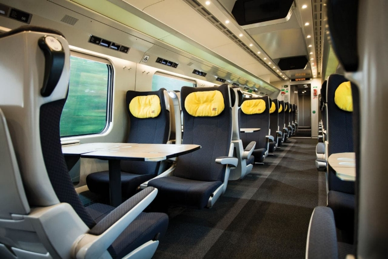 Image on the interior of a Polish PKP train including tables and seats with yellow cushions