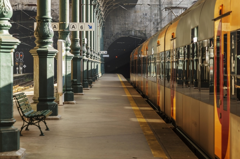 Image of Porto train station with a yellow train parked next to a tunnel and railway platform