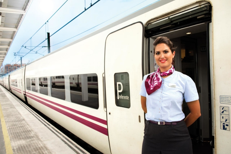 Image of Spanish RENFE train attendant standing in the doorway of a high speed train