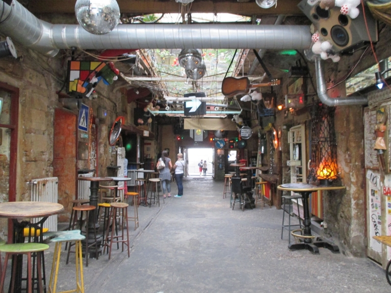 Image of ruin pub in Budapest with tables and stools, and decorations hanging from the ceiling.
