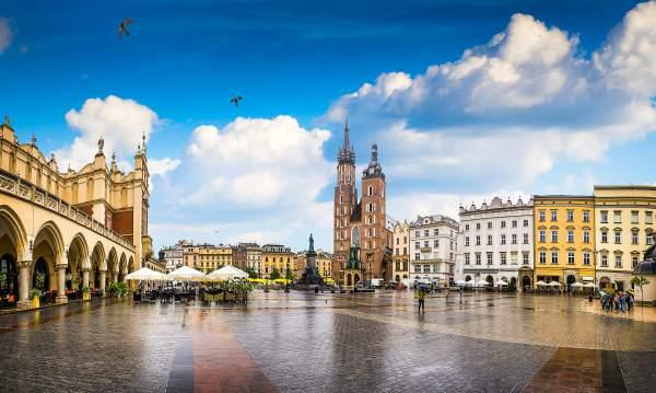 Image of a spacious square in Krakow with yellow buildings and a blue sky