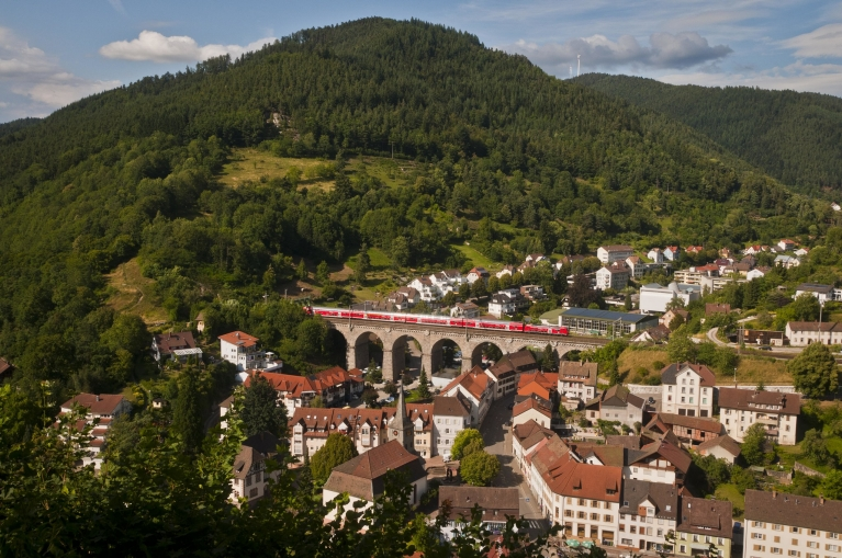 Image of a red train crossing a viaduct in the forested, hillside Black Forest village of Hornberg