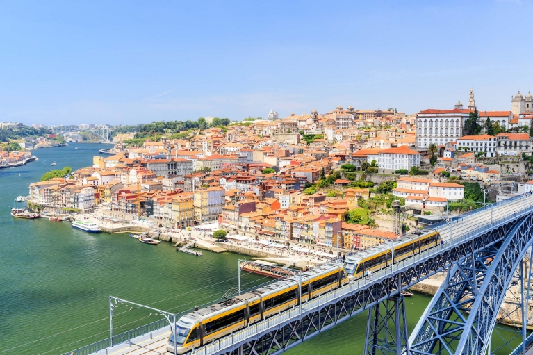Image of a yellow train crossing a high bridge over the Douro river and compact terracotta buildings of Porto