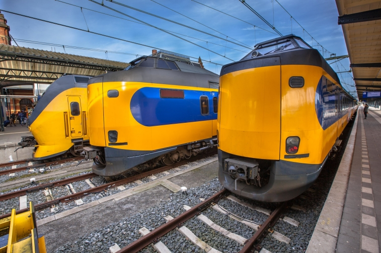 Image of 3 yellow and blue stationary trains on the tracks of Groningen railway station