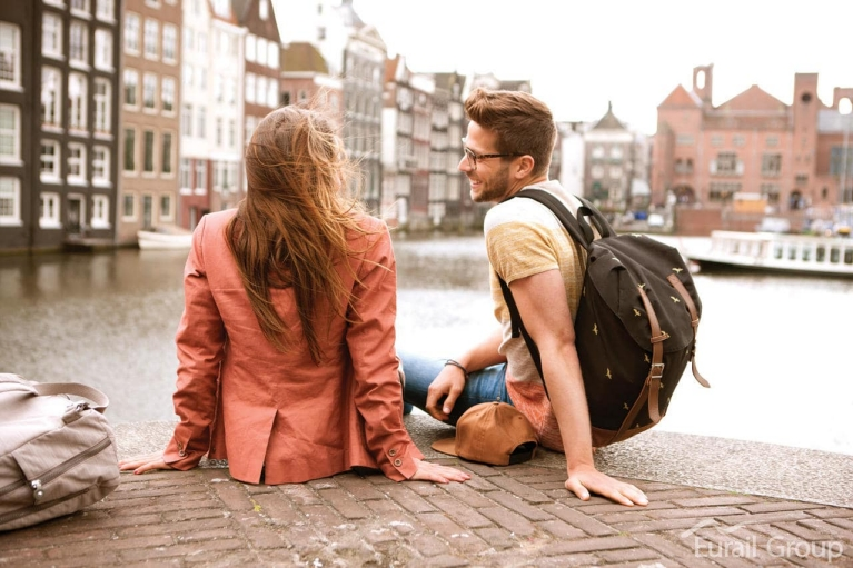 Photo d'un couple assis au bord d'un canal à Amsterdam
