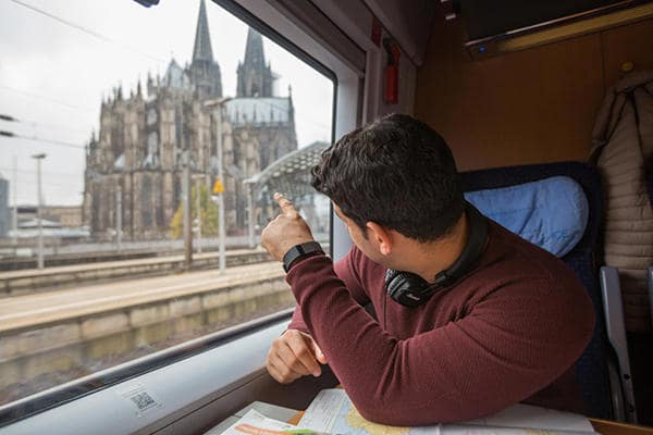 Young man looking at Cologne Cathedral from a train window in Germany